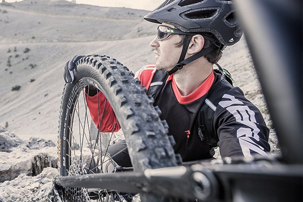 A close up of a MTB rear wheel and a profile view of a MTB'er in a helmet and sunglasses holding his rear wheel