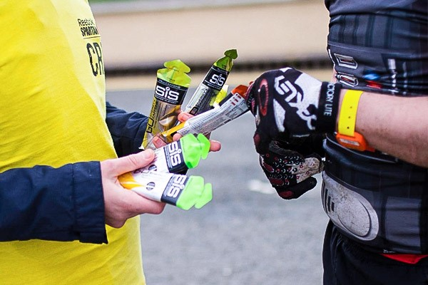 A steward showing a cyclist a range of SiS Energy gels on offer.