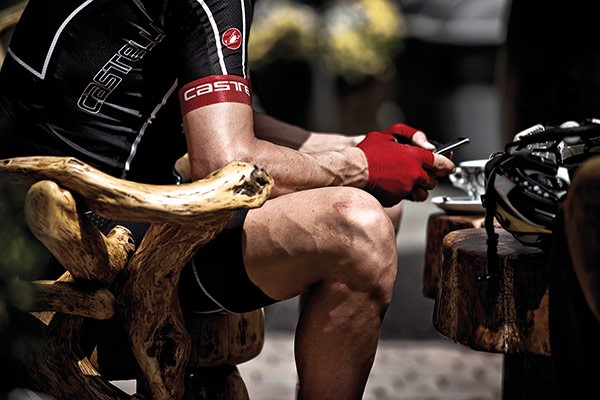 A road cyclist taking a break on a bench using his phone