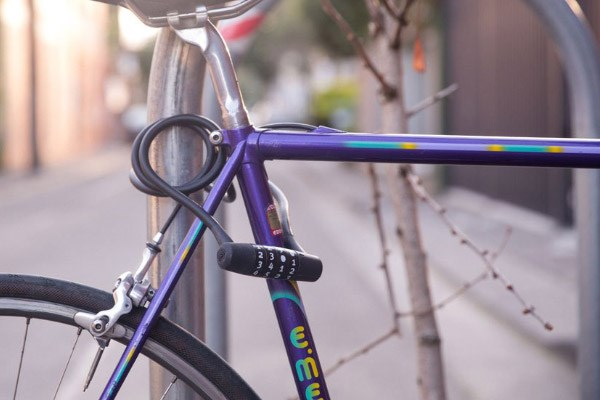 A purple bike frame locked up to a post using a combination cable lock
