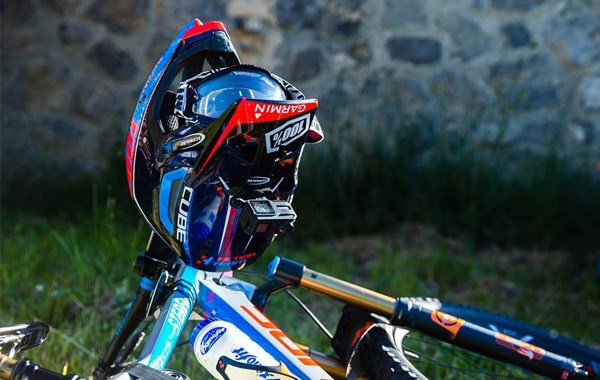 Full face helmet and google rest on the bars of a Cube Stereo