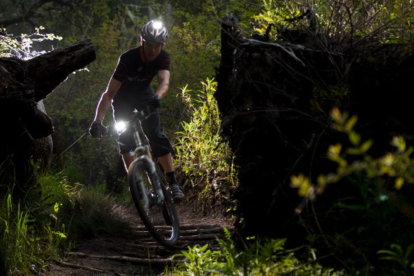 Mountain biker using lights mounted to both the handlebars and their helmet