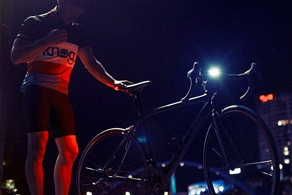 Cyclist adjusting front and rear bike lights
