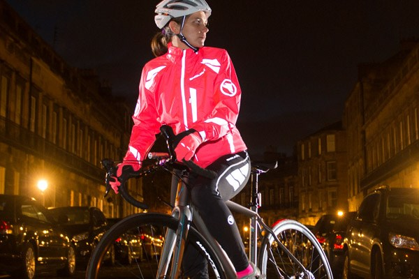 Female cyclist wearing bib tights, riding through the city at night