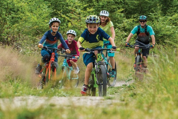 A group of children on kids bikes cycling off-road