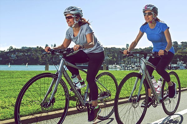 Two female cyclists on hybrid bikes