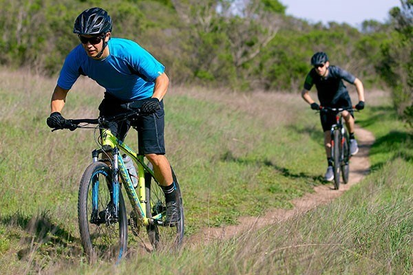 Two cyclists on mountain bikes riding a trail