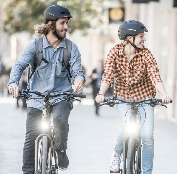 A couple cycling away in a urban setting both wearing helmets